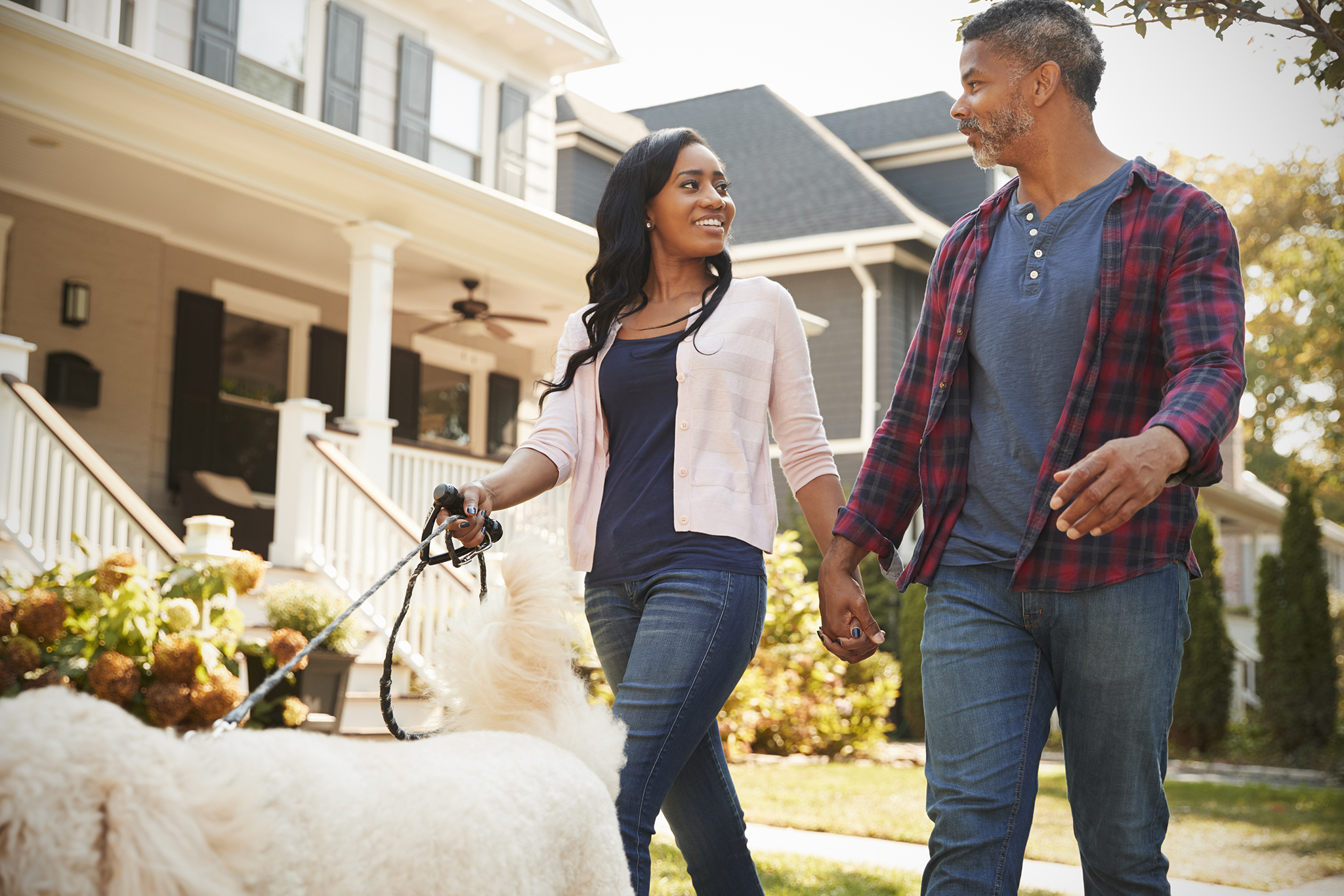 couple-walking-dog-along-suburban-street-PLH8K3F