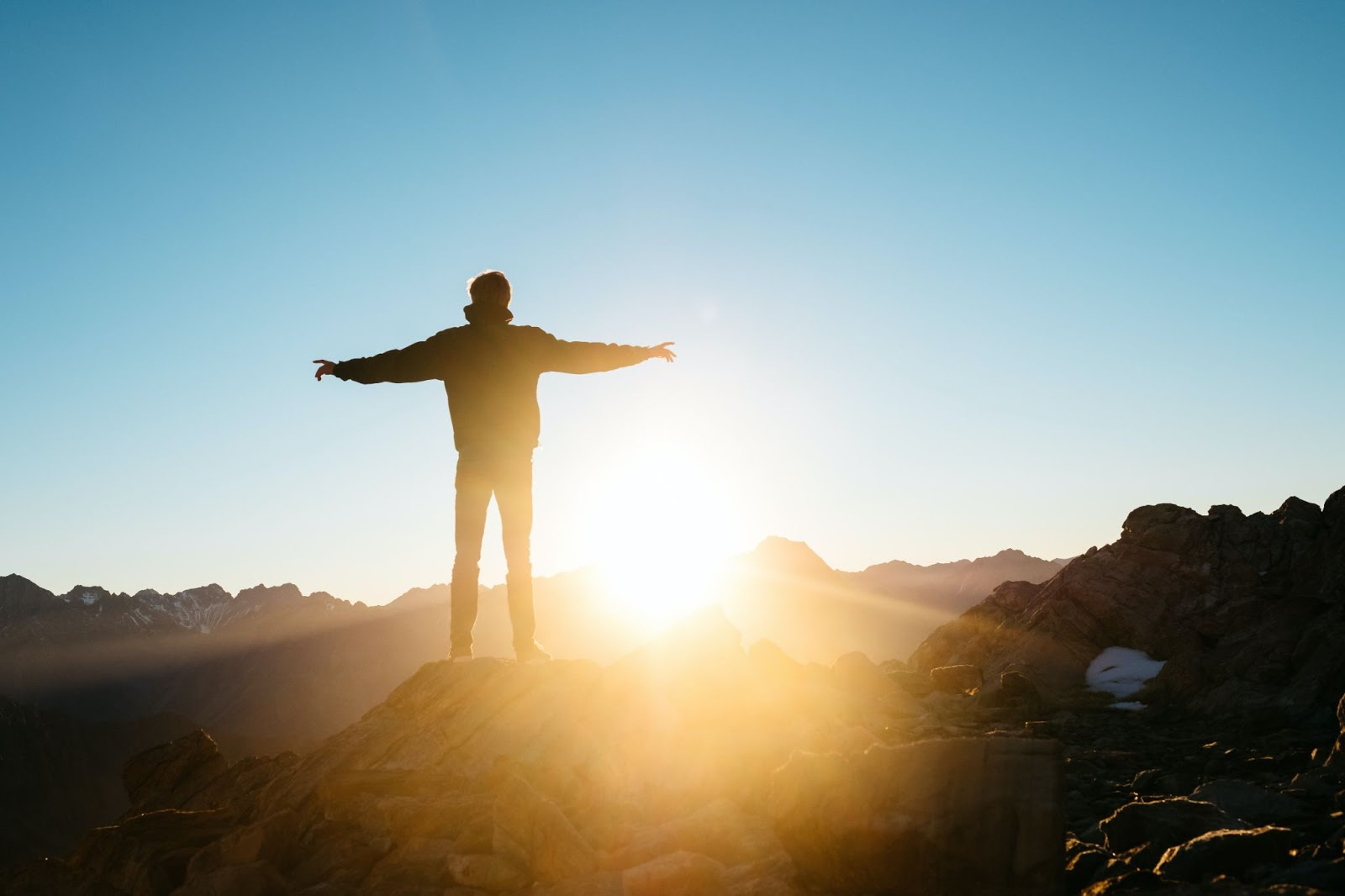 Person facing a sunrise with their arms outstretched, photo by Pablo Heimplatz, sourced from Unsplash